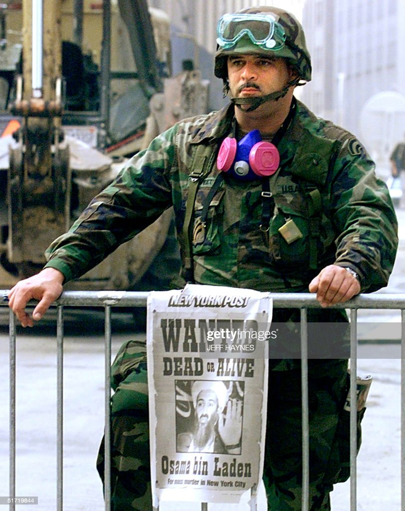 A member of the US National Guard stands behind a wanted post for Osama bin Laden produced by a local newspaper 18 September 2001 in New York. Invoking the rough justice of the Old West, US President George W. Bush said that Osama bin Laden is wanted 'dead or alive' and warned Afghanistan's rulers they must turn him over or pay a steep price. AFP PHOTO/Jeff HAYNES