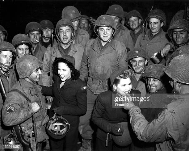 A member of the US O troupe gives a G I a few words of encouragement while the other girl samples a doughnut for another GI December 10 1944