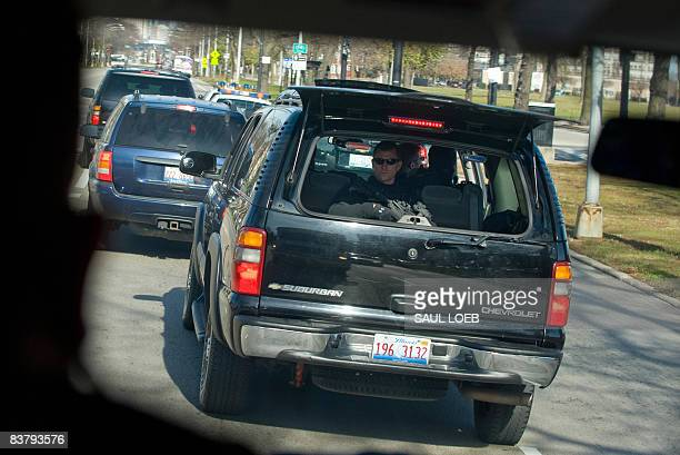A member of the US Secret Service looks out the back of an SUV as US Presidentelect Barack Obama's motorcade drives through the streets of Chicago on...