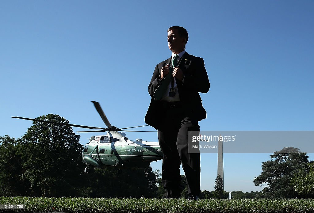 A member of the US Secret Service stands guard as Marine One carrying US President Barack Obama takes off from the South Lawn of the White House on June 29, 2016 in Washington, DC. President Obama is traveling to Canada to attend the North American Summit, where he will meet the leaders from Canada and Mexico, and address a joint session of the Canadian parliament.