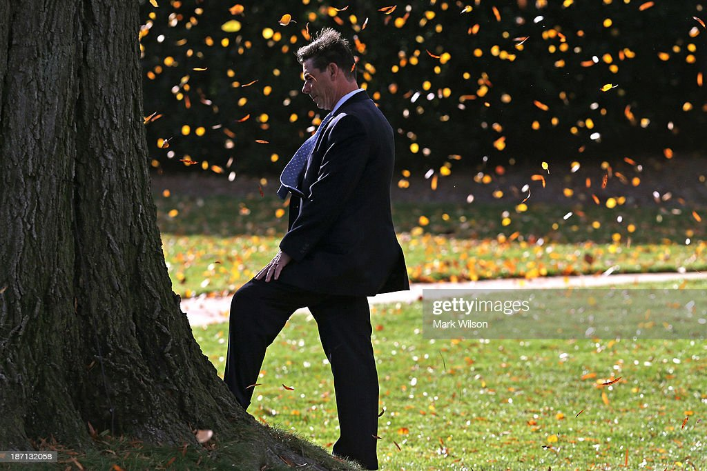 A member of the U.S. Secret Service uses a large tree to block blowing leaves caused by Marine One landing on the South Lawn of the White House November 6, 2013 in Washington, DC. President Obama is traveling to Dallas, Texas to attend fundraisers and talk about the Affordable Health Care Act.