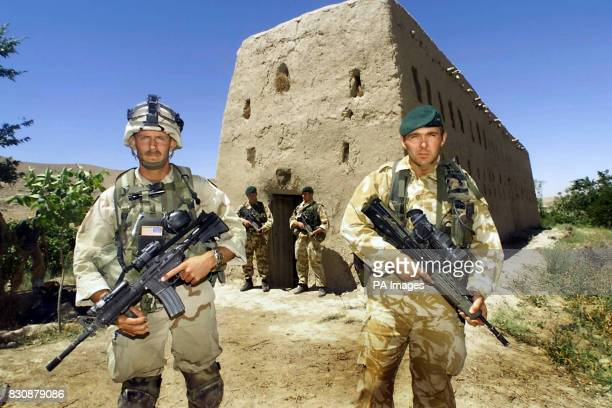A member of the US special forces stands with a British Royal Marine outside the mudbrick barn in Atalay village 50 miles northwest of Kandahar in...
