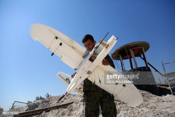 A member of the USbacked Syrian Democratic Forces made up of an alliance of Arab and Kurdish fighters inspects on March 29 2017 a downed drone...