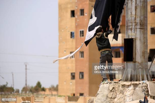 A member of the USbacked Syrian Democratic Forces made up of an alliance of Arab and Kurdish fighters removes an Islamic State group flag in the town...