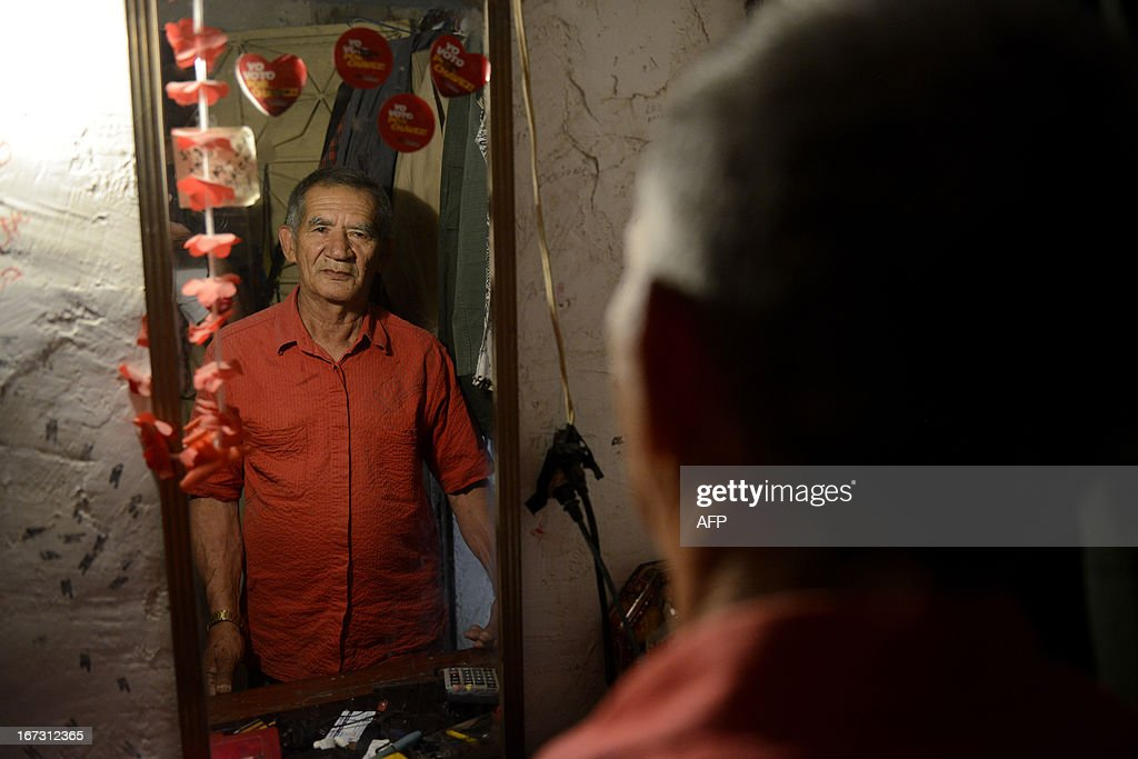 Member of the Venezuelan Militia, Miguel Guevara, 73, stands in front of a mirror dressed as civilian, at his home in Catia, a poor neighbourhood in west Caracas, on April, 20, 2013. Guevara is one of the 130,000 men and women members of the Militias --cretaed by the late President Hugo Chavez in 2005-- who assures he will continue defending Chavez's revolution with his life. AFP PHOTO/Leo Ramirez