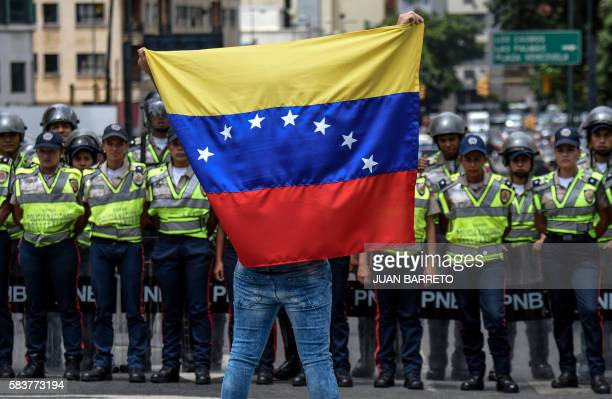A member of the Venezuela's opposition shows a national flag in front of National policemen during a demonstration in Caracas on July 27 2016...