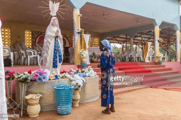 A member of the Very Holy Church of Jesus Christ of Baname arrives at the Nazareth church in Djidja on February 25 2017 at the beginning of a service...