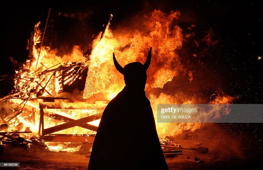 A member of the Viking Jarl Squad is silhouetted in front of a burning viking galley ship during the annual Up Helly Aa Festival Lerwick Shetland...