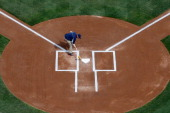 A member of the Washington Nationals grounds crews prepares the batters box before the start of the Washington Nationals and Miami Marlins opening...