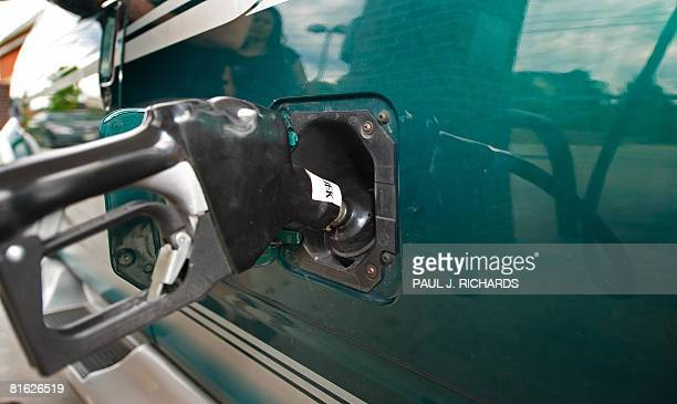 A member of the WJFKFM radio team drops USD 20 of free gasoline into a listener's car on June 18 2008 at a 711 store in Rockville Maryland a suburb...
