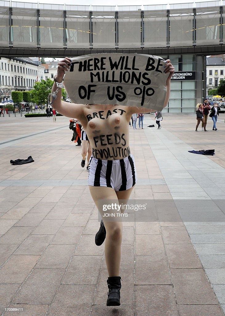 A member of the women's topless protest group Femen holds a banner as she takes part in a protest on June 12, 2013 in front of the European Union Parliament in Brussels, to support a detained Tunisian activist and four other Femen, two French and one German, arrested in Tunis for baring their breasts outside the main courthouse on May 29, in solidarity with a Tunisian activist who had been arrested 10 days earlier.