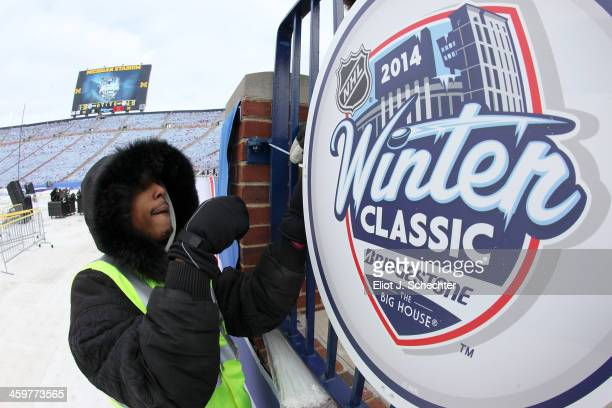 A member of the work crew puts up signage during the 2014 Bridgestone NHL Winter Classic Buildout on December 30 2013 at Michigan Stadium in Ann...