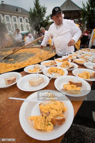 A member of the World Brotherhood of the Huge Omelet attends the making of a 6500 egg omelet within a 4 metre diameter frying pan on August 15 2017...