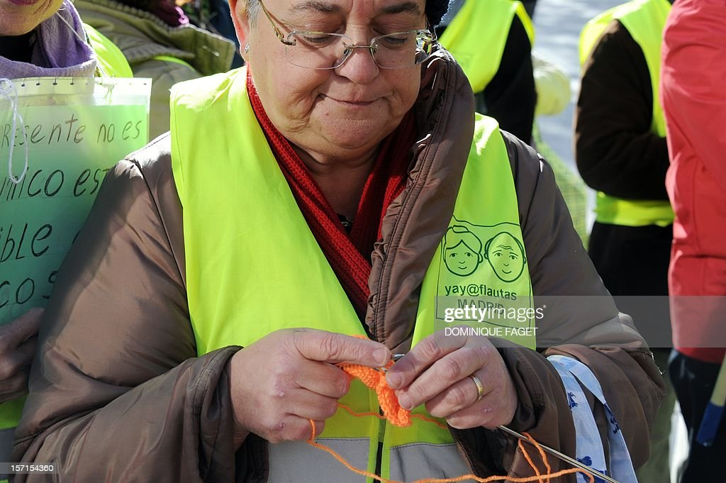 A member of the 'yayoflautas' organization knits during a demonstration organized by anti-eviction activists on November 29, 2012 in Madrid. The Spanish government announced on November 15, 2012, a two-year halt to evictions of the most vulnerable homeowners following an outcry over suicides linked to a surge in mortgage-related expulsions. AFP PHOTO / DOMINIQUE FAGET