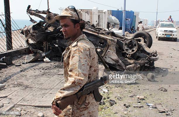 A member of the Yemeni security forces stands next to the wreckage of a vehicle on January 18 in the aftermath of a suicide car bombing on the...
