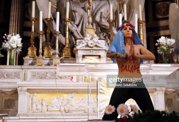 A member of Ukrainian feminist group Femen stands at the altar of the Madeleine church in Paris in a protest against the Catholic Church's stance on...