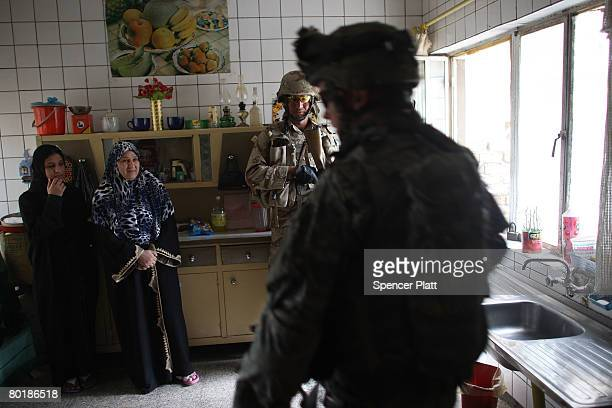 A member of US Army Eagle Company 22 Cavalry Regiment walks past two women while searching their home on a patrol in the Hadar neighborhood with the...