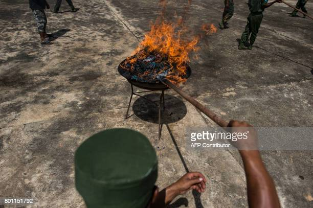 TOPSHOT A member of UWSA sets a pile of seized drugs on fire during a drug burning ceremony to mark the UN's world antidrugs day in Poung Par Khem...