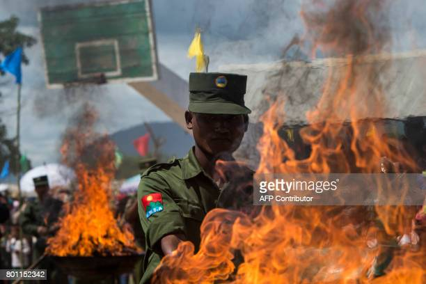 A member of UWSA sets a pile of seized drugs on fire during a drug burning ceremony to mark the UN's world antidrugs day in Poung Par Khem near the...
