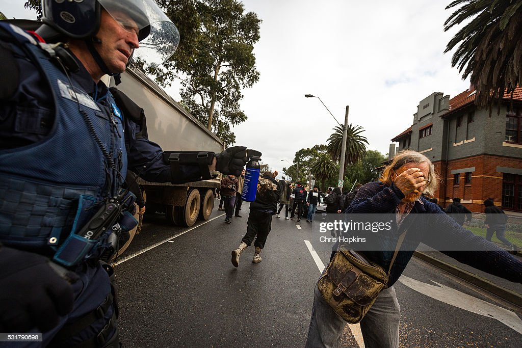 A member of Victoria Police looks on as a member of the anti racism group staggers after being sprayed with capsicum sprayon May 28, 2016 in Melbourne, Australia. Violence erupted when participants in a 'Say No To Racism' rally protesting the forced closure of Aboriginal communities, off-shore detention centres and Islamophobia met with a counter 'Anti-Islam rally organised by the True Blue Crew and backed by the United Patriots Front.
