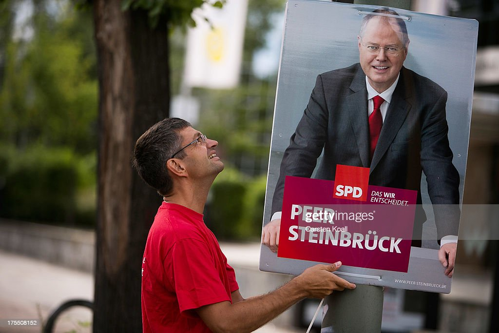 SPD- Member Oliver Schworck, Councilman in the district parliament, hangs an election campaign posters showing German Social Democrats (SPD) chancellor candidate Peer Steinbrueck on August 4, 2013 in Berlin, Germany. Germany is scheduled to hold federal elections on September 22 and so far current Chancellor Angela Merkel and her party, the German Christian Democrats (CDU), have a strong lead over the opposition.