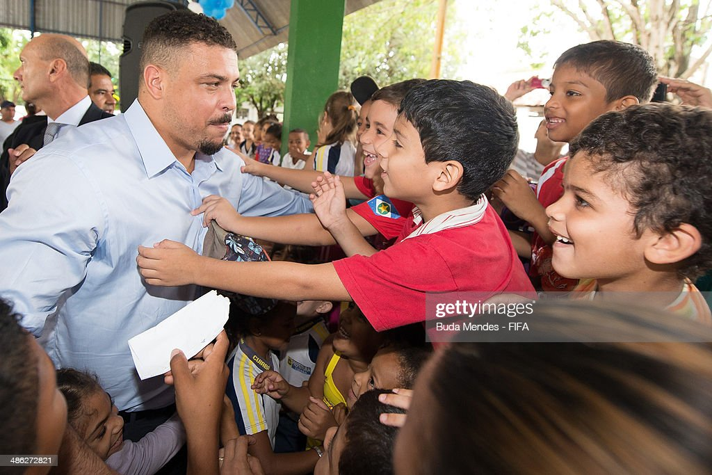 LOC Member Ronaldo Luis Nazario (L) greets the kids during visit the FIFA 11 for Health Program as part of the 2014 FIFA World Cup Host City Tour on April 23, 2014 in Cuiaba, Brazil