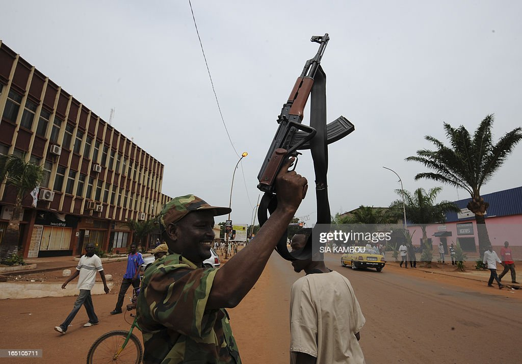 A member the rebel Seleka coalition poses with a kalashnikov automatic weapon during a support march for new Central African Republic leader Michel Djotodia in the streets of Bangui on March 30, 2013. The Central African Republic's new strongman Michel Djotodia vowed Saturday not to contest 2016 polls and hand over power at the end of the three-year transition he declared after his coup a week ago.