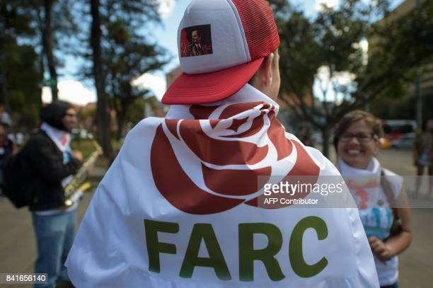 TOPSHOT FARC members and supporters march waving flags with the new logo of the rebaptized FARC transformed into a political party following its...