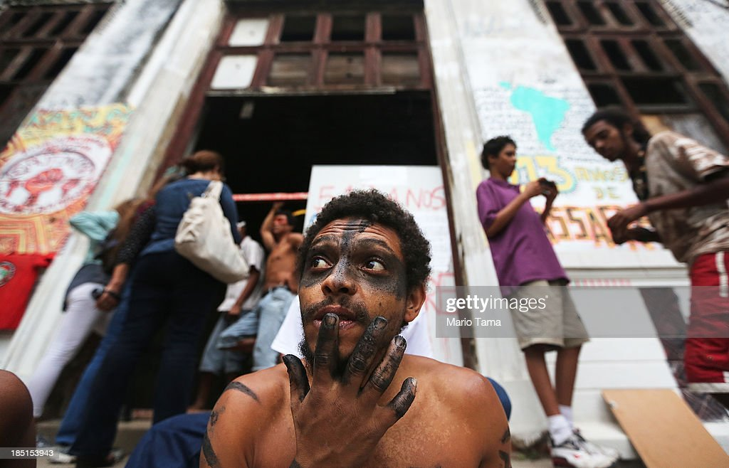Members and supporters of an indigenous community gather in front of the Aldeia Maracana building they are occupying next to Maracana Stadium, the site of the 2014 World Cup final, on October 17, 2013 in Rio de Janeiro, Brazil. The fading structure used to house the Museum of Indian Culture before deteriorating and becoming occupied by squatting indigenous members in 2006. The building was slated for destruction ahead of the 2014 World Cup and the community was forcibly evicted in March. However, the community has managed to return and thus far have successfully battled to save the structure, which they hope to convert into an indigenous university. Indigenous groups throughout Brazil are battling the Brazilian government over land rights and other issues.