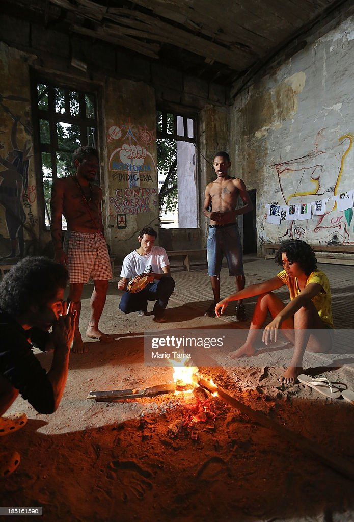Members and supporters of an indigenous community gather in the Aldeia Maracana building they are occupying next to Maracana Stadium, the site of the 2014 World Cup finals, on October 17, 2013 in Rio de Janeiro, Brazil. The fading Aldeia Maracana used to house the Museum of Indian Culture before deteriorating and becoming occupied by squatting indigenous members in 2006. The building was slated for destruction ahead of the 2014 World Cup and the community was forcibly evicted in March. However, the community has managed to return and thus far have successfully battled to save the structure, which they hope to convert into an indigenous university. Indigenous groups throughout Brazil are battling the Brazilian government over land rights and other issues.