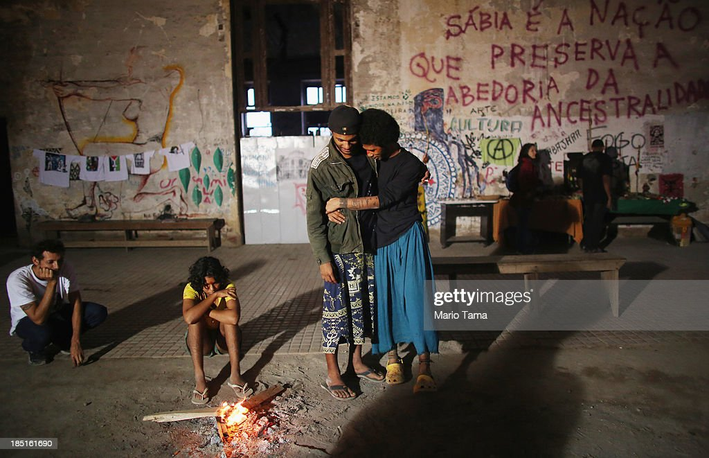 Members and supporters of an indigenous community gather in the Aldeia Maracana building they are occupying, next to Maracana Stadium, the site of the 2014 World Cup finals, on October 17, 2013 in Rio de Janeiro, Brazil. The fading Aldeia Maracana used to house the Museum of Indian Culture before deteriorating and becoming occupied by squatting indigenous members in 2006. The building was slated for destruction ahead of the 2014 World Cup and the community was forcibly evicted in March. However, the community has managed to return and thus far have successfully battled to save the structure, which they hope to convert into an indigenous university. Indigenous groups throughout Brazil are battling the Brazilian government over land rights and other issues.