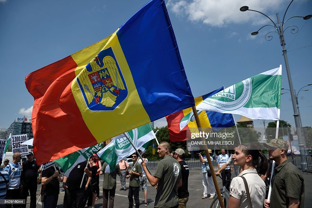Members and supporters of far-right party Noua Dreapta (The New Right) march downtown Bucharest on June 25, 2016 as they protest against gay people and gay marriage. / AFP / DANIEL