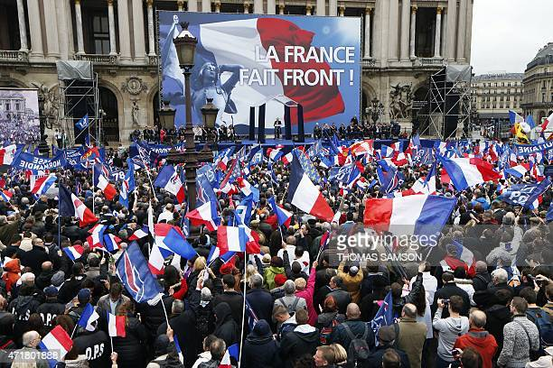 Members and supporters of France's farright Front National party hold French flags as they attend a speech by FN president Marine Le Pen on the Place...