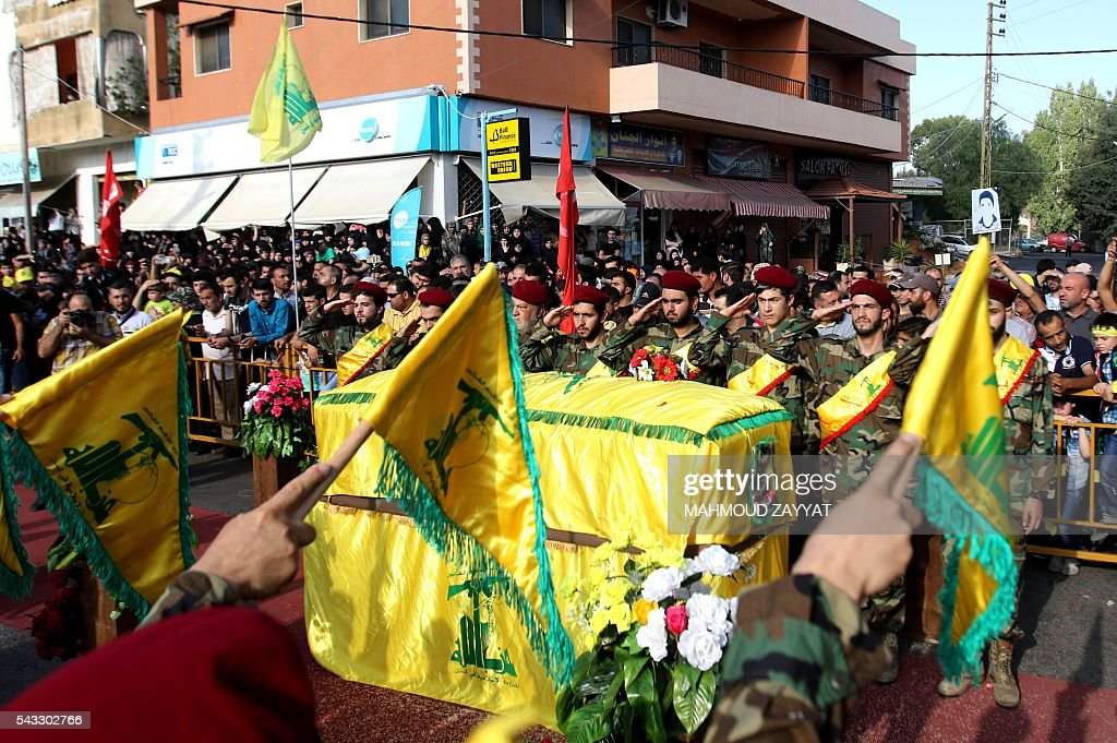Members and supporters of Lebanon's Shiite militant group Hezbollah salute in front of the coffin of Mohammed Ibrahim Hamza who was killed fighting in Syria, during his funeral in the southern Lebanese town of Sharqiyeh, on June 27, 2016. / AFP / MAHMOUD