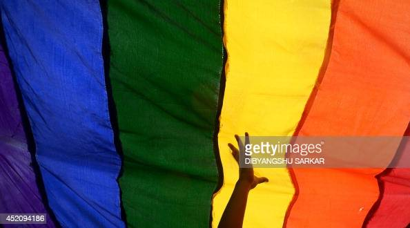 Members and supporters of the lesbian gay bisexual transgender community walk with a rainbow flag during a rally in Kolkata on July 13 2014 Hundreds...