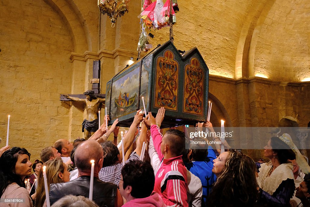 Members congregation and gypsies sing and pray while casket with the reliquary of the local saintes Mary Salome and Mary Jacobe is lifted on May 25, 2016 in Saintes-Maries-de-la-Mer near Arles, France. Gypsies from all over Europe worship 'Sara the Black', their Saint and patroness, for one week. Sara's statue is situated in the crypt of the church.