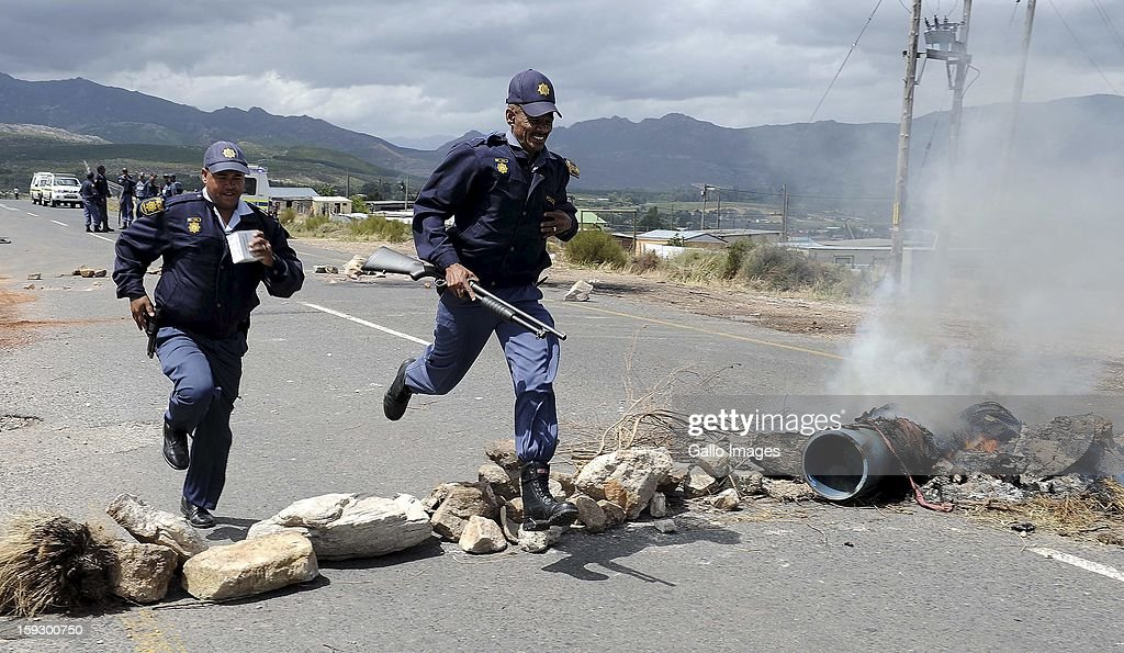 SAPS members control protestors on the N2 highway on January 10, 2013 in Grabouw, South Aifrca. Striking farm workers have blocked the highway as they continue striking.