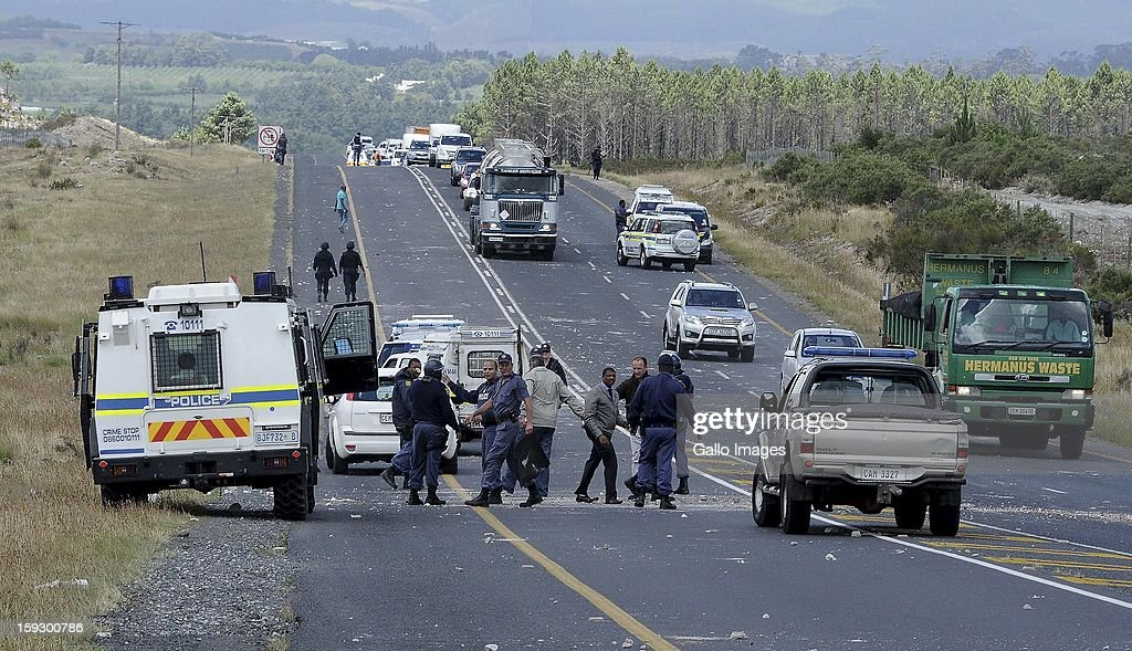 SAPS members control traffic and assist motorists on the N2 highway on January 10, 2013 in Grabouw, South Aifrca. Striking farm workers have blocked the highway as they continue striking.