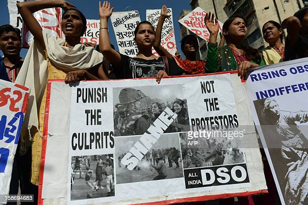 Members from The All India Democratic Students' Organization hold posters as they take part in a protest in Ahmedabad on December 24 following the...