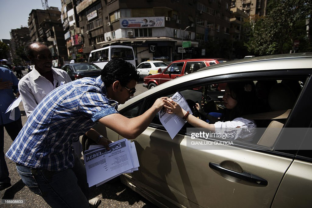 Members from the Tamarod (rebellion) campaign try to collect signatures from motorists to demand Morsi's resignation during a demonstration against Morsi in Egypt's landmark Tahrir square on May 17, 2013. Hundreds of people marched on Cairo's Tahrir Square calling for Morsi to resign and demanding early elections, AFP correspondents and local media reported.