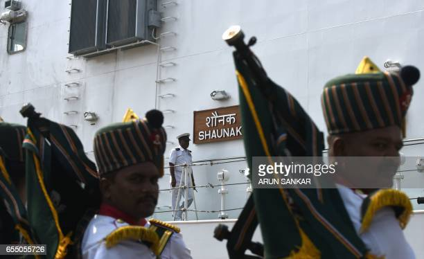 Members of a bagpipe band look on as Indian Coast Guard Ship Shaunak a new offshore patrol vessel arrives at port in Chennai on March 19 making her...