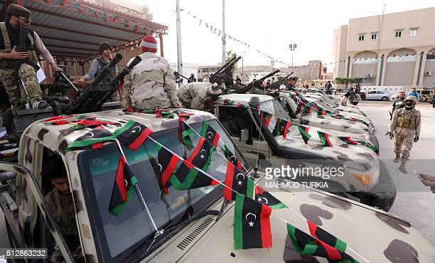 Members of a brigade loyal to the Fajr Libya an alliance of Islamistbacked fighters stand on a pick up trucks mounted with machine guns during a...