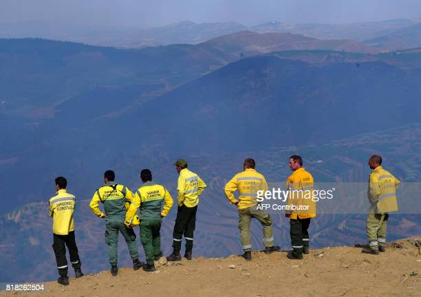 Members of a brigade stand on a cliff after a wildfire near the village of Santa Eugenia in Alijo on July 18 2017 A month after the deadliest forest...