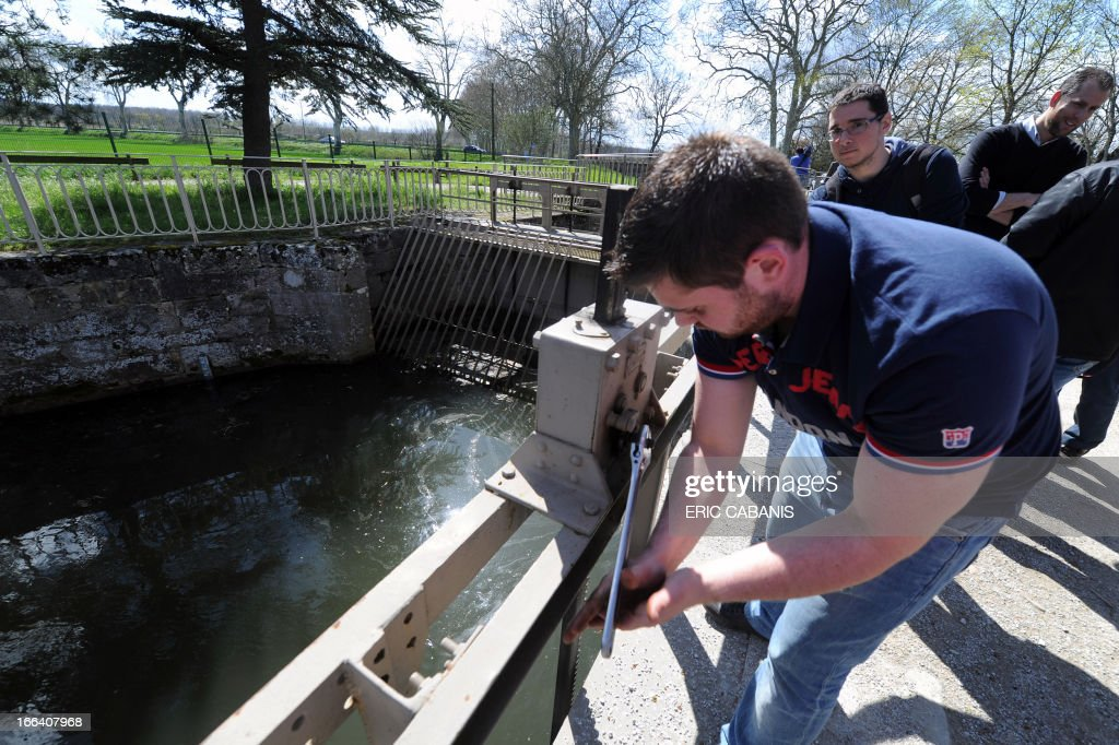 Members of a buisness manager collective in Tarn turn off the feed valve of the Canal du Midi on April 12, 2013 near lake Saint-Ferreol (Haute-Garonne), the basin feeding the canal, as they request for the construction of a highway between Toulouse and Castres.