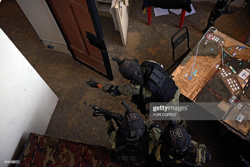 Members of a command of the Mexican army special forces throw a grenade as they perform urban combat maneuvers at the 37-B Military Camp in Temamatla, Mexico state on April 30, 2013. Mexican Special Forces' members will take part in a special security operation during the visit of US President Barack Obama in Mexico City next May 2. AFP PHOTO/ Yuri CORTEZ