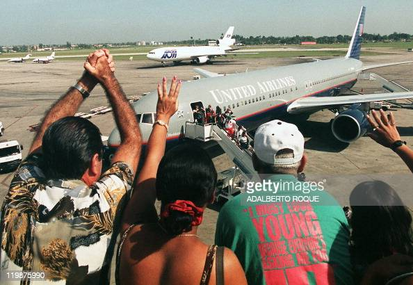 Members of a Cuban family wave to relatives arriving from Miami on a United Airlines airplane chartered by ABC Charters 15 July at the Jose Marti...