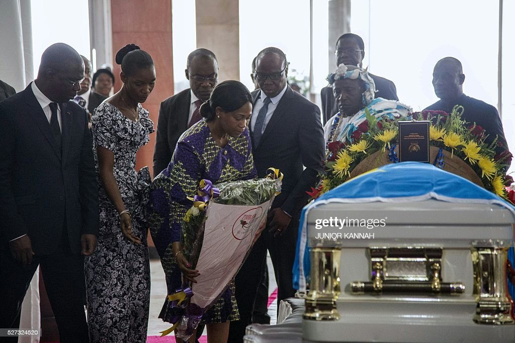 Members of a delegation from the Ivory Coast lay flowers next to the coffin of rumba musician Papa Wemba during his funeral in Kinshasa on May 2, 2016. Democratic Republic of Congo's rumba king Papa Wemba was posthumously awarded one of his country's highest honours, a week after he collapsed on stage and died aged 66. / AFP / JUNIOR