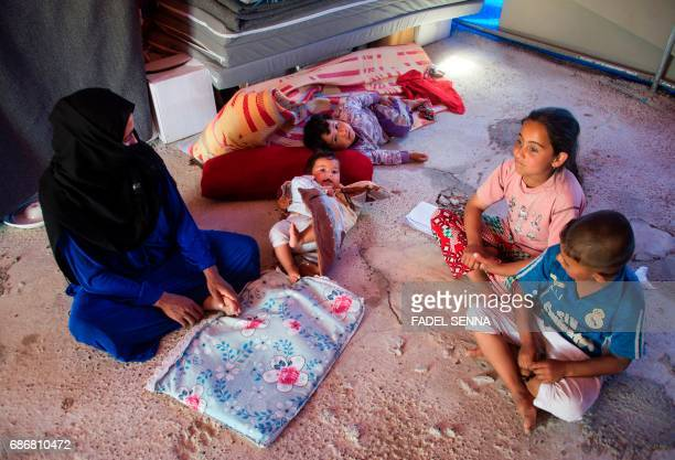 Members of a displaced Iraqi family sit on the ground inside their tent at a camp for Internally Displaced People in Hammam alAlil south of Mosul on...
