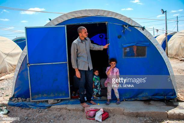 Members of a displaced Iraqi family stand outside their tent at a camp for Internally Displaced People in Hammam alAlil south of Mosul on May 22 2017...