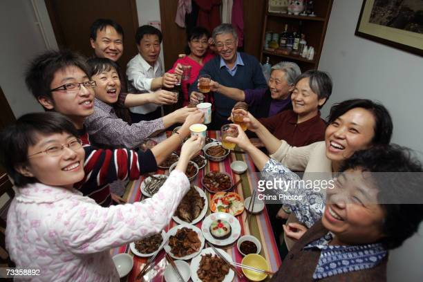 Members of a family toast during New Year's Eve dinner at a resident's home on February 17 2007 in Beijing China The Chinese lunar New Year or the...
